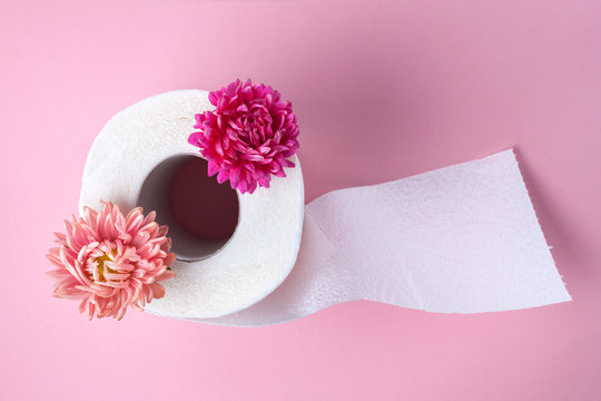 Scented toilet paper roll and a pink flowers on a pink background. Toilet paper with a smell. Hygiene
