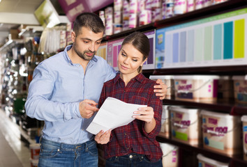 couple is choosing color for paint with shop list