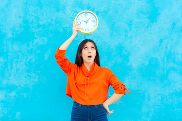 Woman Holding Clock Checking Time on Blue Background