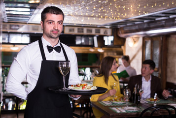 Portrait of frendly male waiter who is standing with tray