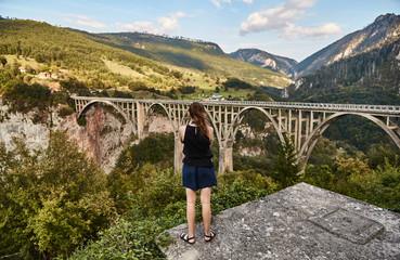 A young girl photographs the bridge Dzhurdzhevicha. Tourist photographs attraction. Montenegro.