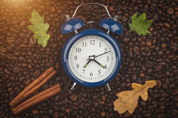 Roasted coffee beans, cinnamon sticks and alarm clock. Wake up. Good morning. Autumn mood. Background, close-up view.