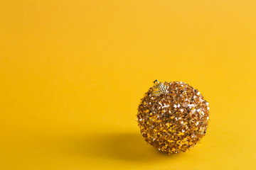 idea of minimal christmas concept, golden christmas ball on yellow background, copy space