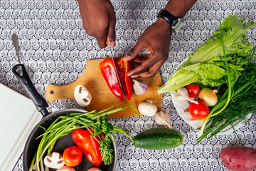 closeup of man hands african american cuts vegetables fry salad pepper, mushrooms, tomato in...