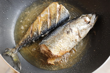 Frying fishes in frying pan.
