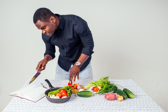 African American chef looking at the recipe book cooking tasty salad slicing vegetables on the table in white background in the studio. healthy menu of homemade food