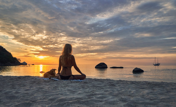 Young woman with dog meditating on the beach and watching dawn