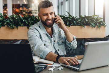 Young happy man sitting in office at table, working on computer, talking on phone.Freelancer has telephone conversations