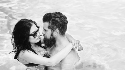 Romantic sensual couple alone in infinity swimming pool over beautiful blue water background. Young and attractive couple hugging in swimming pool. Love story on hot Sunny day. Black and white
