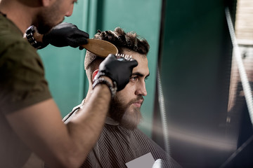 Handsome young man with beard sits at a barber shop. Barber in black gloves shaves hairs at the side.