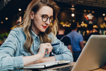 Student girl in trendy glasses sits in cafe in front of computer, laptop watches educational webinar. Online education.