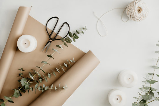 Creating of a bouquet with baby blue eucalyptus branch in a golden wrapping paper among white candles on a table. The concept of a florist work or celebration. Top view, flat lay.