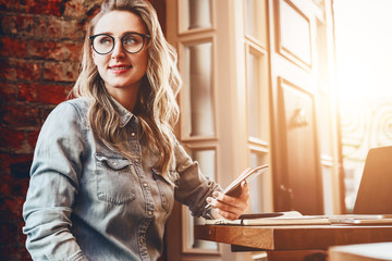 Hipster girl in trendy glasses sits in cafe at table in front of laptop,holding smartphone.Girl looking for friends in restaurant.Businesswoman working remotely. Girl blogger is waiting for followers.