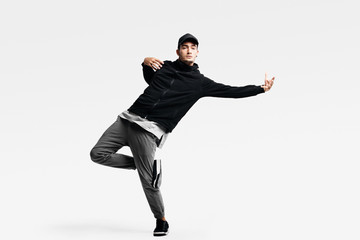 Handsome young man wearing a black sweatshirt, gray pants and a cap dancing street dances on a white background