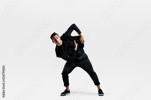 89d5fe0d Stylish young man wearing a black sweatshirt and black pants makes stylized  movements of hip-poh