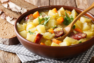 Traditional German kartoffelsuppe potato soup with sausages in a bowl close-up. horizontal