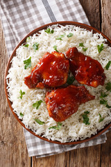 fried chicken thighs with catalina sauce served with rice on a plate. Vertical top view from above