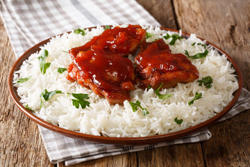 glazed Catalina chicken with spicy sauce and basmati rice close-up on a plate. horizontal