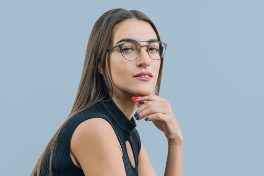 Portrait of young attractive woman with glasses close-up, on blue background, copy space