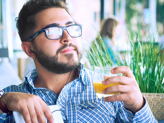 Arabic Egyptian young business attractive man having a coffee break and drinking orange juice in cafe.