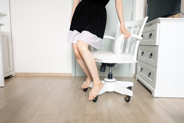 Young Woman Standing. Woman in Black Dress and Pink Nails Manicure. Beautiful Female Slim Legs with Barefeet in the White Room at Condo Background
