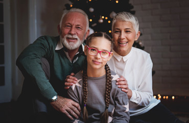 Grandparents and their granddaughter gathered around a Christmas tree, smiling