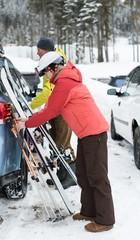 Senior couple keeping ski board and ski pole near car