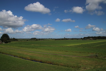 meadows of the Zuidplaspolder at Moordrecht, the lowest area of western europe in the Netherlands in wide area view with blue sky and white clouds.
