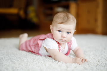 Portrait of baby girl in white sunny bedroom. Newborn child learning crawling.