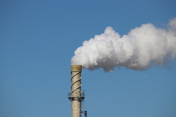 Steam comes out a chimney above a factory with white steam cloud on clear blue sky in Rotterdam