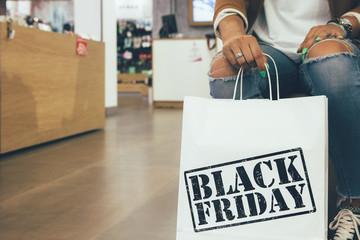 Female shopper holds shopping bag