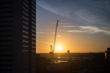 Construction jobsite panoramic view at sunset/sunrise with cranes and machinery