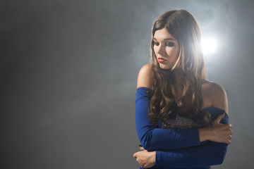 beauty young woman in blue dress on gray background