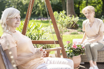 Smiling senior woman on hanging chair in the garden with caregiver