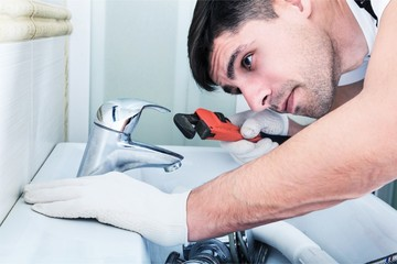 Handsome Professional plumber fixing pipes. Plumbing repair