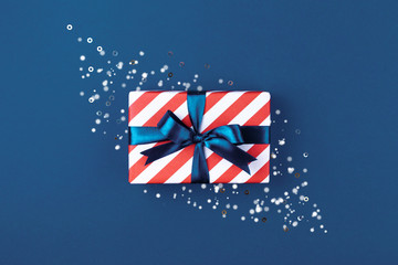 Gift box wrapped in red striped paper and tied with blue bow on blue background decorated with sparkles. Christmas card concept.