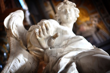 "Detail of the hand of an ancient statue of an angel; concept photo to express ideas like ""stop"", ""touch"", ""take""."