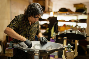 Craftsman designing handpan iCraftsman in his workshop making design and construction of Handpan, a metal percussion instrument.nstrument