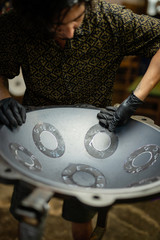 Craftsman in his workshop making design and construction of Handpan, a metal percussion instrument.