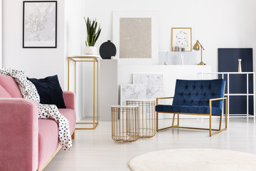 Silver abstract painting on the wall of trendy living room with two elegant coffee tables, petrol blue armchair and powder pink couch with doted blanket on it