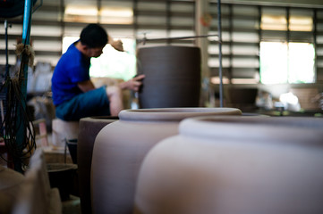 Closeup picture of traditional clay pottery in the factory with blurred worker working in background
