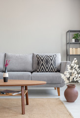 Wooden table in front of grey settee in simple apartment interior with flowers and carpet. Real photo