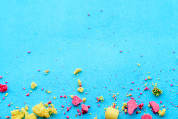 Blue background with multicolored cake crumbs, top view
