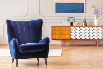 Close-up of a dark blue armchair with a vintage cabinet in the background in a living room interior