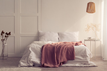 pink blanket on white bed in minimal bedroom interior with lamp above table with plant. Real photo