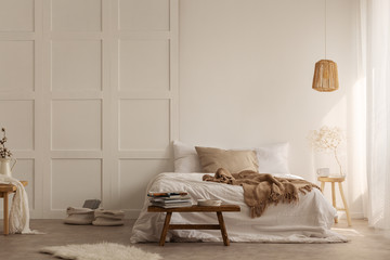 Natural blanket on white bed in simple bedroom interior with fur next to wooden stool. Real photo