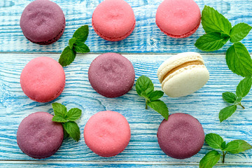 Sweet macarons on a blue  background. Trendy cakes.