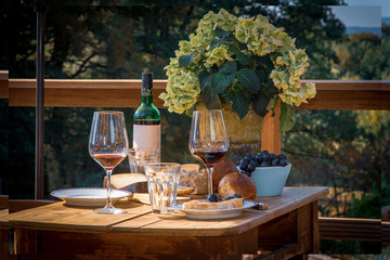 old wooden table with wine, bread and cheese in summer