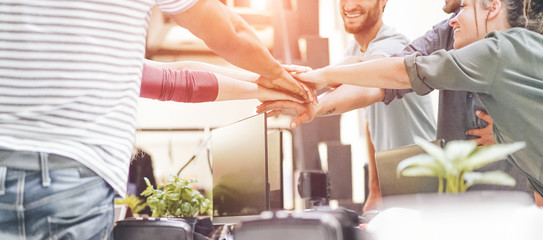 Young teamwork stacking hands together for new startup in creative office