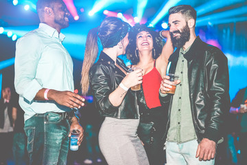 Happy friends having party and drinking bee in night club